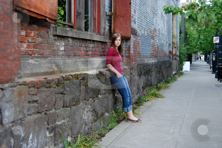 Teen Leaning Against Wall stock photo, Outdoor shot of a teenage girl with her hands in her pockets leaning against a brick and stone wall. by Orange Line Media