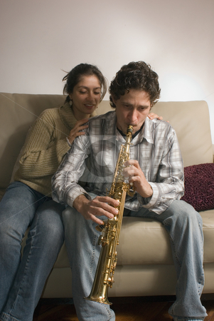 A Young Couple with a Soprano Saxophone stock photo, A young man paying a soprano saxophone next to a smiling woman sitting on a sofa with her hands resting on the man's shoulders listening. by Orange Line Media