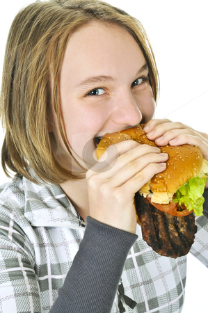 Teenage girl holding big hamburger stock photo, Teenage girl holding a big hamburger isolated on white background by Elena Elisseeva