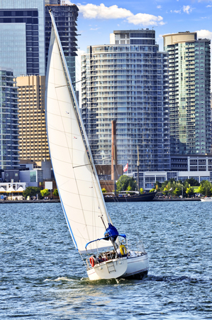 Sailboat in Toronto harbor stock photo, Sailboat sailing in Toronto harbour with downtown view by Elena Elisseeva