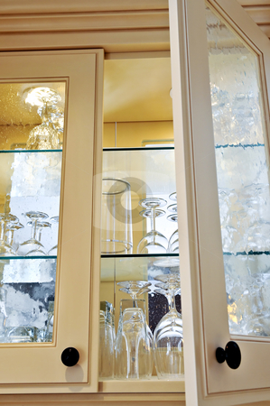 Kitchen cabinet stock photo, Kitchen cabinet close up with glass shelves and glasses by Elena Elisseeva