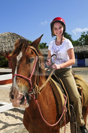 Girl riding horse stock photo, Young girl riding brown horse wearing helmet by Elena Elisseeva