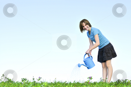 Girl with watering can stock photo, Smiling teenage girl with watering can on green grass by Elena Elisseeva
