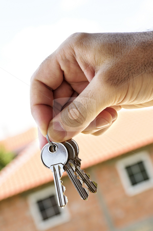 Hand holding keys stock photo, Man's hand holding keys with a house under construction in background by Elena Elisseeva
