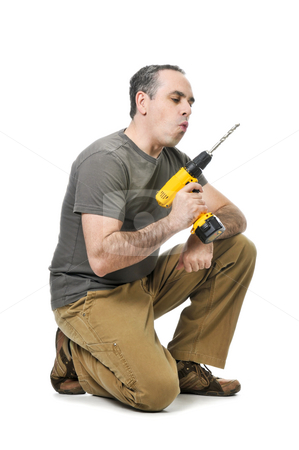 Handyman with a drill stock photo, Kneeling handyman blowing on his cordless drill by Elena Elisseeva