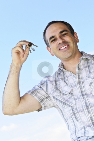 Man holding keys stock photo, Smiling man holding house keys on blue sky background by Elena Elisseeva