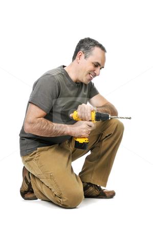 Handyman with a drill stock photo, Kneeling handyman pushing on his cordless drill by Elena Elisseeva
