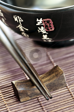 Rice bowl and chopsticks stock photo, Asian rice bowl and wooden chopsticks on a rest close up by Elena Elisseeva