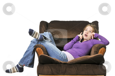 Teenage girl talking on a phone stock photo, Teenage girl talking on a phone sitting in an armchair by Elena Elisseeva