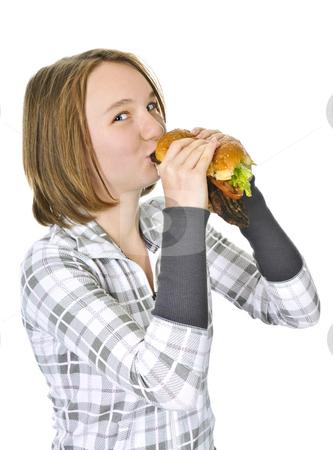 Teenage girl holding big hamburger stock photo, Teenage girl holding a big hamburger isolated on white background by Elena Elisseeva