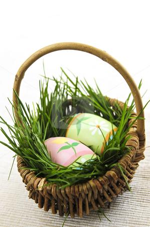 Easter eggs with green grass stock photo, Easter eggs arrangement with green grass in a basket by Elena Elisseeva