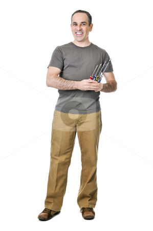 Handyman with screwdrivers stock photo, Smiling handyman holding a bunch of screwdrivers by Elena Elisseeva