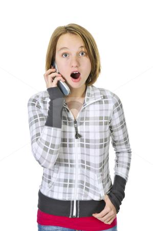Teenage girl talking on phone stock photo, Teenage girl talking on a cell phone acting surprised isolated on white background by Elena Elisseeva