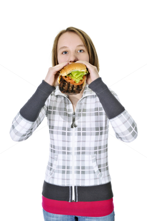 Teenage girl eating big hamburger stock photo, Teenage girl eating a big hamburger isolated on white background by Elena Elisseeva