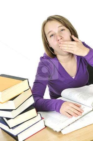 Teenage girl studying stock photo, Yawning teenage girl studying at the desk by Elena Elisseeva