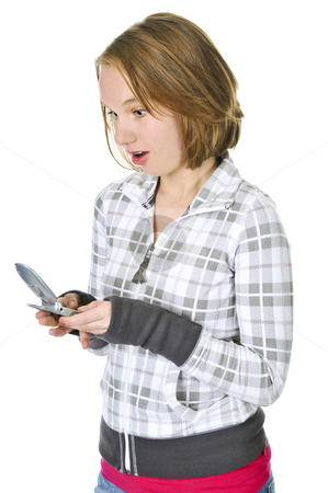 Teenage girl text messaging on a cell phone stock photo, Teenage girl text messaging on a cell phone isolated on white background by Elena Elisseeva