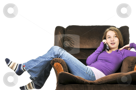 Teenage girl talking on a phone stock photo, Teenage girl talking on a phone sitting in an armchair by Elena Elisseeva