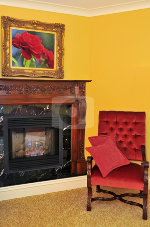 Fireplace and red chair stock photo, Fireplace and red chair, image on the wall is my own by Elena Elisseeva