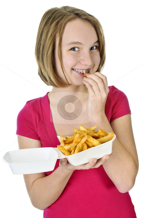 Teenage girl with french fries stock photo, Teenage eating french fries isolated on white background by Elena Elisseeva