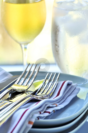 Plates and cutlery stock photo, Table setting with stack of plates and cutlery by Elena Elisseeva