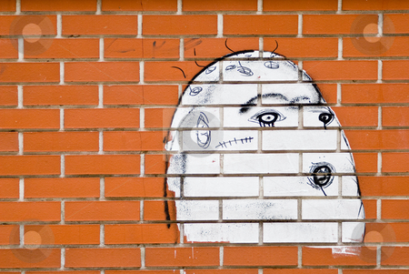 Face on the wall stock photo, A brickwall with a graffiti showing an ugly white face by Alexander L?