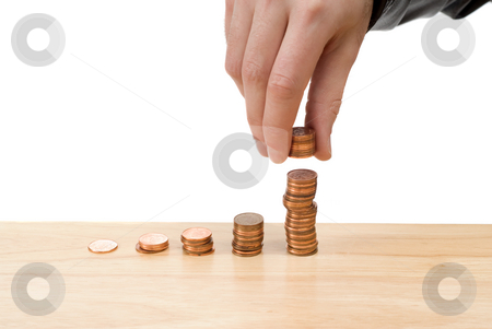 Increasing Savings stock photo, Stacks of pennies growing progressively higher with a hand adding more to the highest one, with copyspace by Richard Nelson