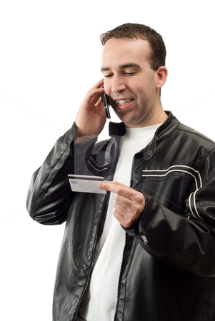 Paying By Phone stock photo, A young man using his credit card to pay for something on a cell phone, isolated against a white background by Richard Nelson