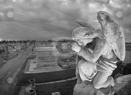 Praying Statue Cemeteryscape stock photo, A praying statue kneels on top of a tomb in New Orleans under moody skies.  High point of view to contain the cemetery landscape in the background. by A Cotton Photo