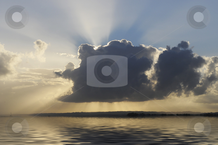 Breaking through stock photo, Sun is breaking through a dark cloud over  calm water by Magnus Johansson