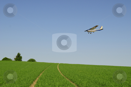 Incoming stock photo, Perfect green farmland with small airplane flying over by Magnus Johansson