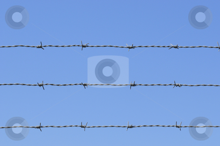 Barb wire sky stock photo, Barb wire against blue sky by Magnus Johansson