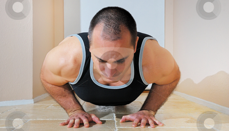 Strong Man Doing Pushups stock photo, Strong man in tanktop doing pushups on the floor. by Denis Radovanovic