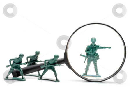 Army Men stock photo, A toy soldier being investigated under a magnifying glass. by Robert Byron