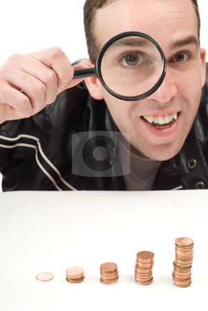Profits stock photo, A man looking happy while looking through a magnifying glass, is excited about his profits by Richard Nelson