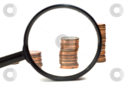 Examining Profits stock photo, Closeup view of a magnifying glass looking at a stack of pennies, isolated against a white background by Richard Nelson