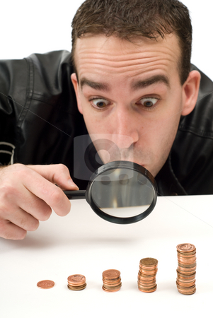 Man Looking At Money stock photo, A young guy looking at his money with a magnifying glass by Richard Nelson