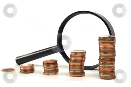 Looking At Money stock photo, A magnifying glass and stacks of pennies shot against a white background by Richard Nelson