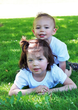 Brother and Sister stock photo, Cute young siblings in the park together. She is lying on the grass and he is sitting up behind her. Horizontally framed shot. by Orange Line Media