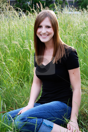 Teen Sitting in Field - Vertical, Smiling stock photo, Vertically framed outdoor shot of a smiling teenage girl sitting in a field with green grass. by Orange Line Media