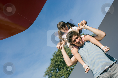 Girl Riding on Dad's Shoulders stock photo, Horizontally framed outdoor shot of a cute little girl, pigtails,  riding on her dad's shoulders. by Orange Line Media