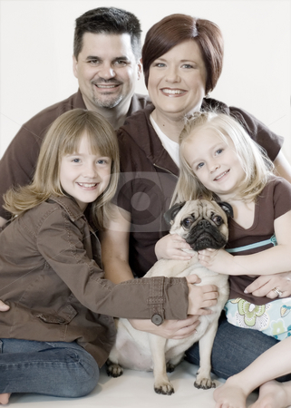 Family Portrait stock photo, Family of four and their pug posing together in a studio. Vertically framed shot against a clean studio background by Orange Line Media
