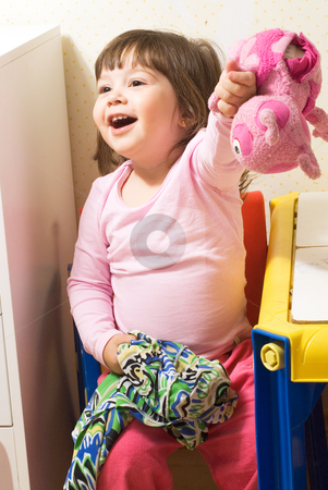 Girl with Toys stock photo, Adorable little girl sitting on a chair holding out a stuffed animal and smiling by Orange Line Media