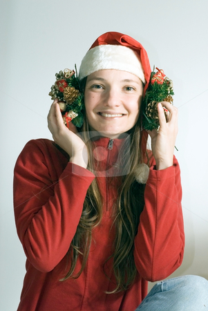Young Woman in a Santa Hat stock photo, Attractive young woman clowning around with decorations while wearing a santa hat and smiling at the camera. Set against a gray studio background. by Orange Line Media