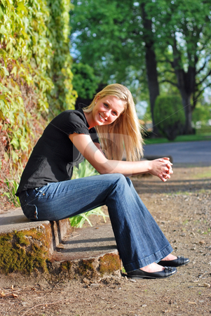 Attractive Blond Woman stock photo, Attractive young blond woman casually dressed smiling at the camera sitting on some stone steps in golden evening light by Orange Line Media