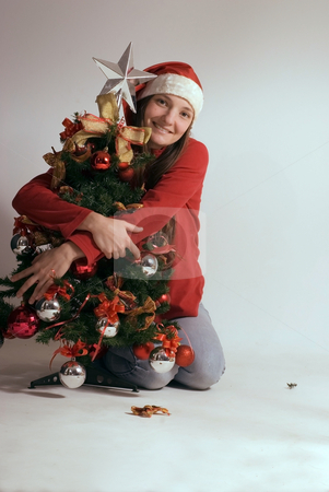 Young Woman and Christmas Tree stock photo, Attractive young woman wearing a red fleece and santa hat hugging a miniature Christmas tree. Isolated against a gray studio background. by Orange Line Media