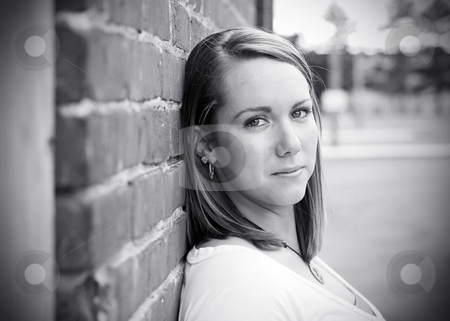 Teen Leaning Against Wall - Black and White stock photo, Horizontally framed outdoor black and white headshot of a teenage girl leaning up against a brick wall looking at the camera. by Orange Line Media