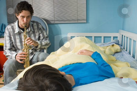 Father and Son - Horizontal stock photo, Young father playing a tune on a saxophone as his son gets ready to fall asleep by Orange Line Media
