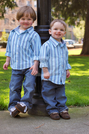 Two Young Brothers stock photo, Outdoors shot of two young brothers wearing identical button-up shirts and blue jeans. by Orange Line Media