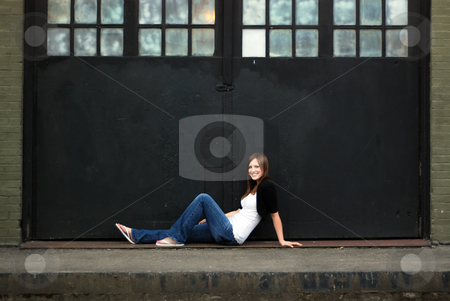 Cute Brunette stock photo, Young attractive brunette stretched out in front of a warehouse door. Horizontally framed wide-angle shot. She is smiling and casually dressed. by Orange Line Media