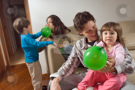 Family of Playing with Balloons stock photo, Horizontally framed indoor shot of a family of four playing with balloons on a sofa. by Orange Line Media